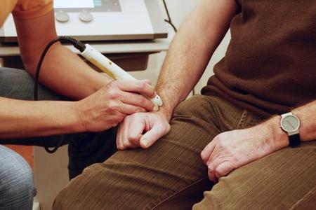 actividad fisica: Fisioterapeuta trata a los pacientes con el RSI en la mu�eca con l�ser Foto de archivo