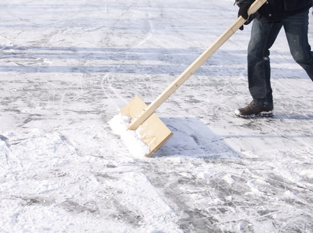 drifting ice: Shoveling snow with wooden shovel from ice for speed ice skating with wooden shovel