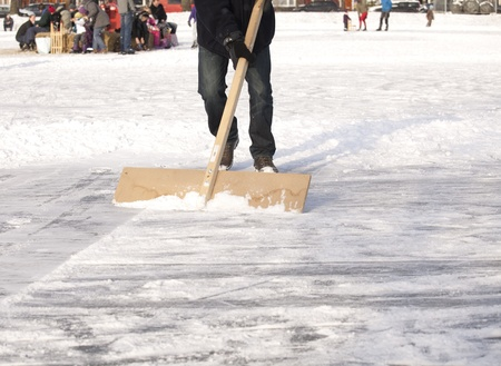 Clearing ice from snow for ice skating photo