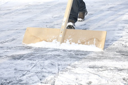 Shoveling snow with wooden shovel from ice for speed ice skating with wooden shovel photo
