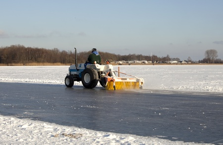 Cleaning outdoor ice on a frozen lake in the Netherlands prior to speed skating tour Editorial