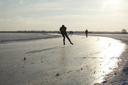THE NETHERLANDS-FEB 9: Ice skaters on frozen lake practising for the Noorderrondritten in the north of Holland on feb 9 2012, a 150 km skating race in Groningen. ' This february  temperatures dropped in the netherlands to an exceptionally low - 20 �C Stock Photo - 12257980