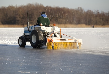 recreational vehicle: Man on machine cleaning frozen lake skating race track