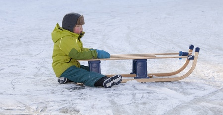wintersport: THE NETHERLANDS-FEB 4:Small tired boy sitting on ice with red cheeks holding on to his sleigh on feb 4, 2012. February is the coldest month throughout the Netherlands with an average of -0.5�C. This february although temperatures dropped to a minus 20 �C