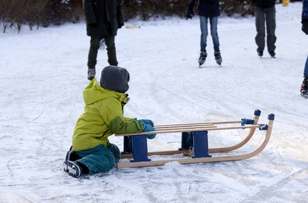 THE NETHERLANDS-FEB 4:Small boy sitting on ice with sleigh looking at skaters on feb 4, 2012. February is the coldest month throughout the Netherlands with an average of -0.5¡C. This february although temperatures dropped to a minus 20 ¡C
