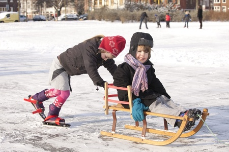 THE NETHERLANDS-FEB 4:Girl on ice skates pushes brother on sleigh on ices on feb 4, 2012. February is the coldest month throughout the Netherlands with an average of -0.5¡C. This february although temperatures dropped to a minus 20 ¡C
