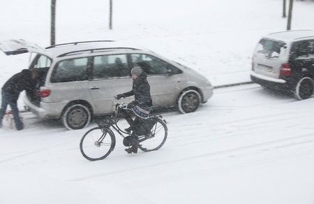 exceptionally: THE NETHERLANDS-FEB 3: Girl bikes through freezing snow blizzard on a Dutch street on feb 3, 2012. February. This february  temperatures dropped in the netherlands to an exceptionally low - 20 �C