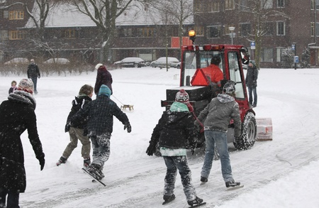 shove: THE NETHERLANDS-FEB 3: Snow shovel at work on natural outdoor ice skating rink with children in pursuit in the Netherlands on Feb 3, 2012.  February is the coldest month throughout the Netherlands with an average of -0.5�C. This february temperatures drop
