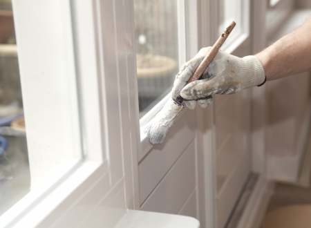 trims: Hand with paintbrush painting a door white Stock Photo