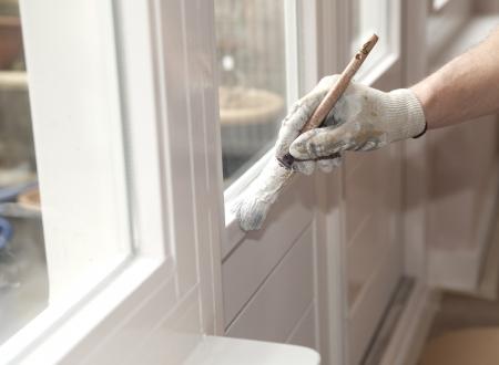 Mano con pincel pintar una puerta blanca Foto de archivo