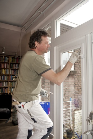 Painter on a ladder painting a door white
