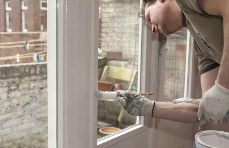 Maler arbeitet an einem Fenster