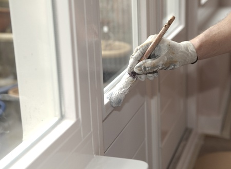 homeownership: Hand with paintbrush painting a door white Stock Photo