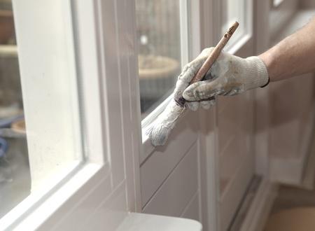 pintor: Mano con pincel pintar una puerta blanca