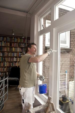 Painter painting inside of door in living room  Standard-Bild