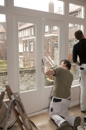 home improvements: Professional painters working in a room Stock Photo