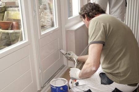 peintre en b�timent: Peintre travaillant � la porte avec de la peinture blanche