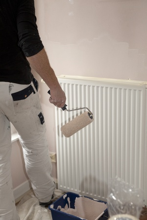 homeownership: Painter with paintroll in hand in front of radiator