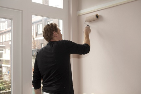 Painter working with paintroller on wall photo