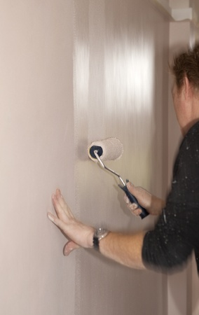 Professional painting with roller in house. Focus on roller. photo