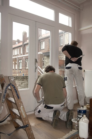 Pair of housepainters at work in a room photo