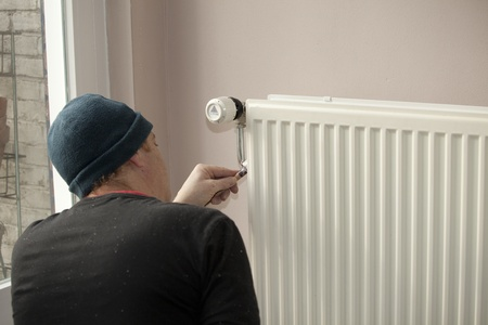 Painting a radiator in concentration Stock Photo - 12754179