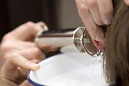 big ear: Doctor cleans ear with water syringe