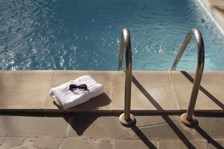 Towel and sunglasses near the swimming pool photo