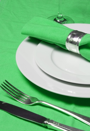 table setting with napkin, silverware and plates on apple green  tablecloth photo