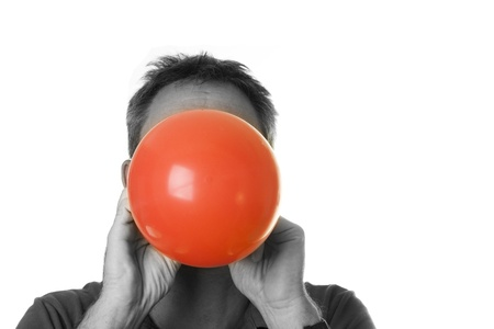 Black and white portrait of man blowing a red balloon Stock Photo - 13162374