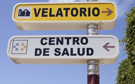 Spanish language signs directing to a health center and a funeral wake building Editorial