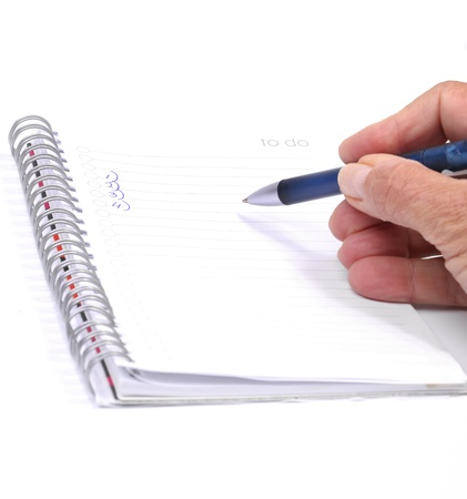 Female hand in blue sweater checking a to do list with written numbers Stock Photo - 13357665