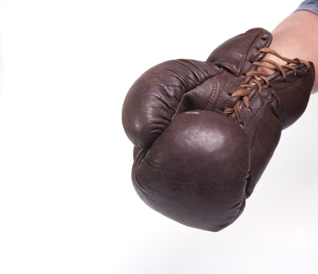 beating: Uppercut punch with a vintage brown boxing glove Stock Photo