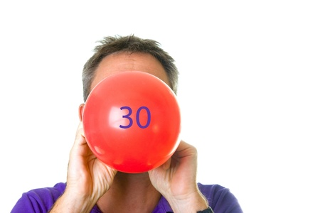 Man blowing red balloon with 30 Stock Photo - 14074547
