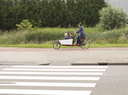 THE NETHERLANDS-JUNE 12:  Dutch mother with three children in transport bike on June 12, 2012. Parents in the Netherlands uses this means of transport to transport their children from and to school Standard-Bild
