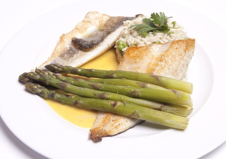 sea bass: Delicious seabass with saffron sauce and risotto with asparagus,  Stock Photo