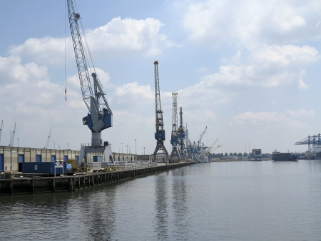 NETHERLANDS- JUNE 26: Container stack and cranes in Rotterdam port on June 26, 2012. Rotterdam is the largest port in Europe and the number three busiet port in the world only surpassed by Shanghai and Singapore.  A large extension of the port of Rotterda Редакционное