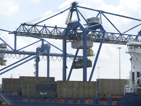 NETHERLANDS- JUNE 26: Industrial crane moving container in harbor of Rotterdam on June 26, 2012. Rotterdam is the largest port in Europe and the number three busiet port in the world only surpassed by Shanghai and Singapore.  A large extension of the port