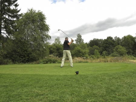 Golf player on the tee makes a swing photo