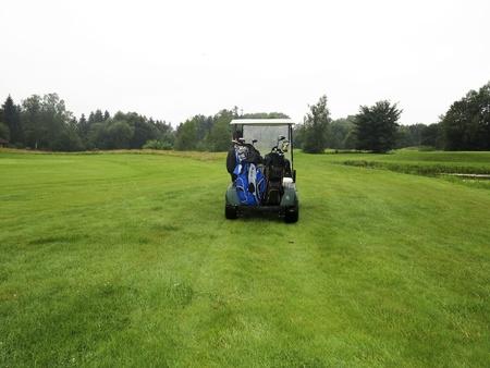 Man in golfcart on fairway in rain photo