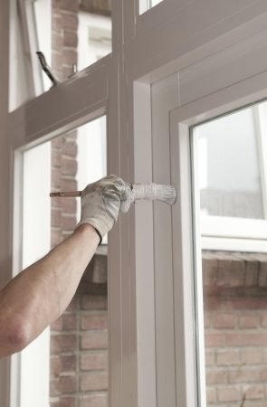 Painting a wooden window with white paint Stock Photo