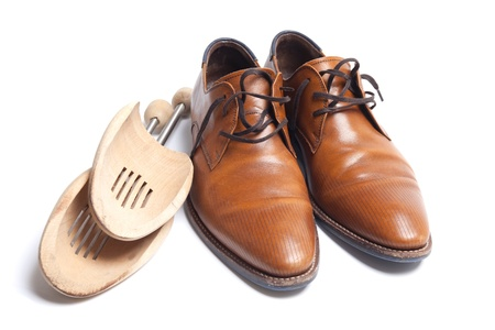 Brown leather mens shoes with wooden shoe stretchers on the side photo