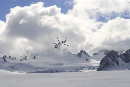 Helicopter flying above Franz joseph glacier in New Zealand photo