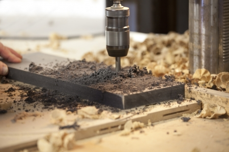 wood cutter: Machine drilling a hole in a piece of black wood with shaving