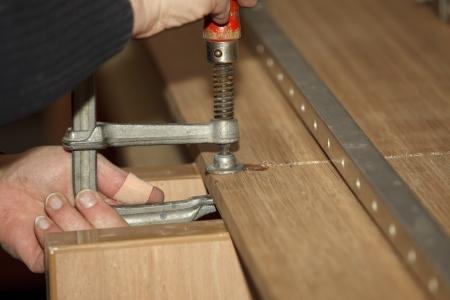 resistol: Carpinteros mano atornillar una abrazadera de pegamento para unir dos tablas