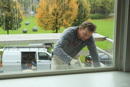 house coats: Painter working outdoors on a window frame