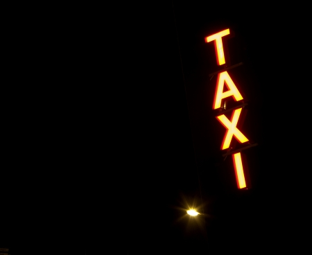 Taxi sign with lamp light at night photo