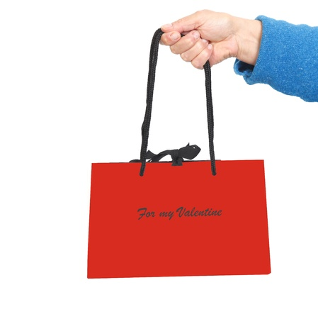 Hand in blue sweater holding red bag with Valentine text Stock Photo - 17365868