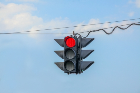 Traffic light on red hanging on wires in the air photo