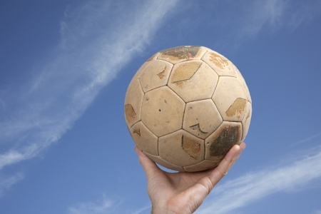 Male hand holding old leather soccer ball against the sky photo